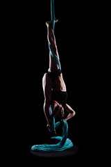 Young woman gymnast with blue gymnastic aerial silks