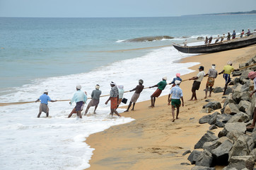 Fishermen are pulling net from the sea in India.