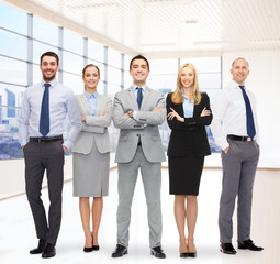 group of smiling businessmen over office room