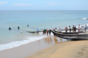 Fishermen are pulling the net from the sea in India.
