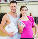 two smiling people with scale in the gym
