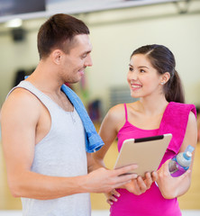 two smiling people with tablet pc in the gym