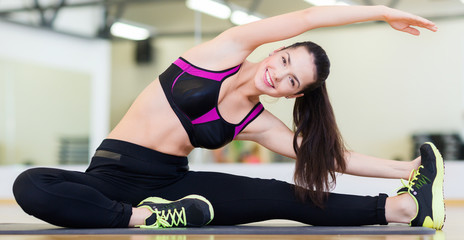smiling teenage girl stretching on mat in the gym