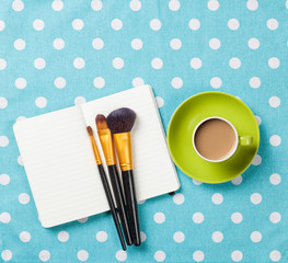 Cup and notebook with makeup brushes