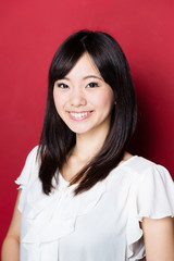 portrait of young asian woman on red background