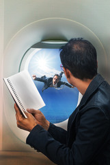 business man reading book in passenger plane seat and looking to