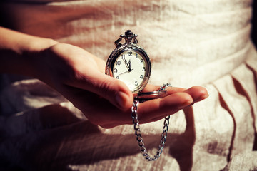 Woman holding antique watch that shows five to twelve time.
