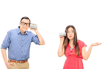 Young couple talking through a tin can phone