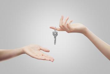 Mani con chiavi sfondo grigio