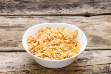 Corn flakes in white bowl on wood background