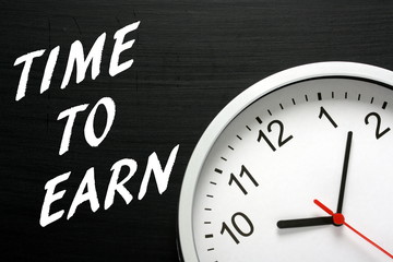 The phrase Time to Earn on a blackboard with a clock