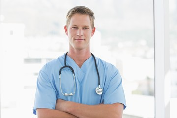 Confident male doctor looking at camera with arms crossed