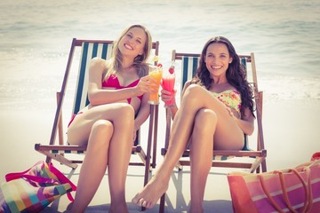 Cute friends having cocktails on the beach