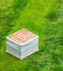 stack of brick paving on the grass