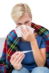 Sick blonde woman blowing her nose and checking the thermometer
