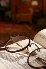 Spectacles and a vintage book on wooden desk