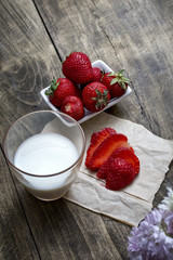 Fresh ripe strawberry in bowl and milk over wooden table backgro