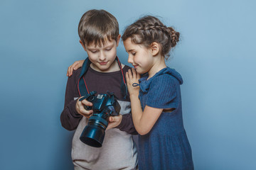 Teenage boy with a girl watching pictures on the camera on a gra