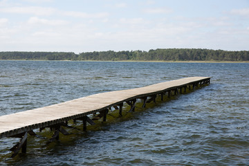 Old wooden pontoon leading to the horizon upon water by blue day