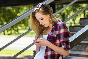 Young beautiful hipster girl typing on smart phone