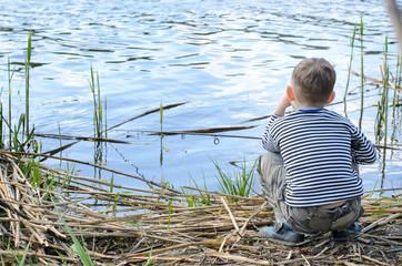 Serious Boy Sitting on Riverside While Fishing
