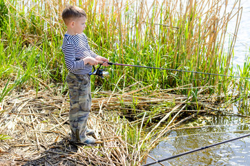 Serious Boy at the Riverside Holding Fishing Rod