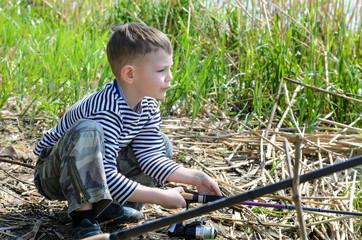 Boy Squatting at the Riverside Holding Fishing Rod