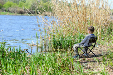 Young Boy Sitting on Chair and Holding Fishing Rod
