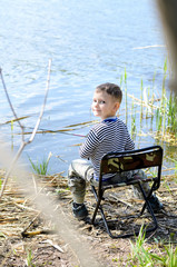 Smiling Young Boy Sitting on a Chair While Fishing