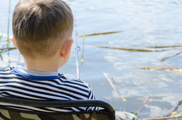 Little boy relaxing fishing at a lake