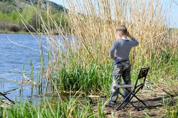 Young boy fishing on a lake shore
