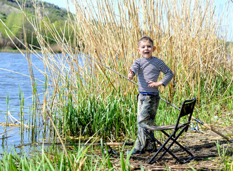 Happy boy giving a thumbs up as he stands fishing