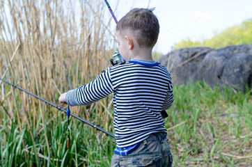 Young boy holding up his fishing rod and reel