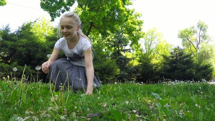 girl blows on a dandelion