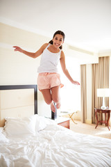 Woman jumping on bed wearing pajamas.