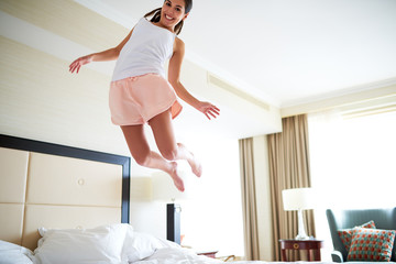Angled view of woman jumping on bed.