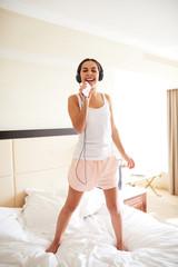 Woman standing on bed wearing headphones.