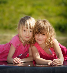 Two young girls laying on a playground
