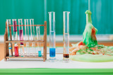 rack with colorful liquids on desk during chemistry class