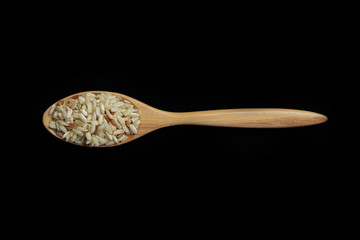 Pile of brown rice with spoon isolated on Black Background