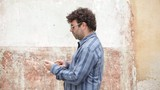 Man walking while writing message in outdoor