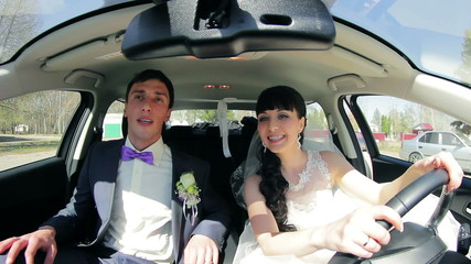 The bride and groom have fun behind the wheel of car. Wedding