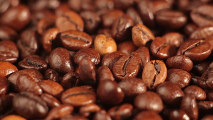 Roasted coffee beans rotates on the table. close-up