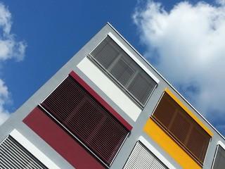 Bunte Rollläden an einem modernen Bürogebäude