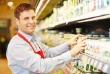 Fototapety Salesman organizing dairy products in supermarket