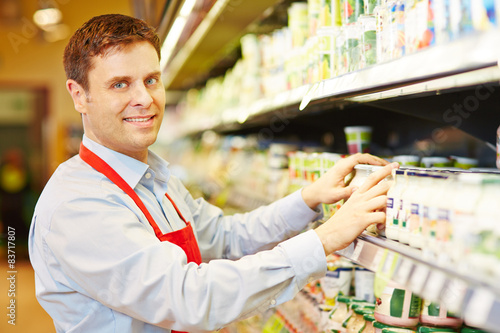 Salesman organizing dairy products in supermarket