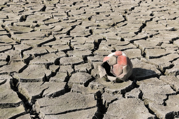 Dry cracked earth and old torn soccer ball