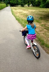 Little girl riding a bike with her helmet on, urban setting