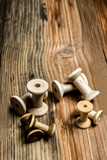 empty wooden sewing spools on old wood background