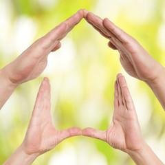 Hände zeigen ein Haus
